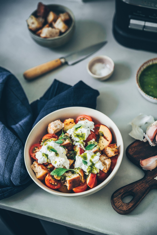 La panzanella vous connaissez ? Cette recette typique de la cuisine pauvre Toscane qui est une simple salade de pain très ancienne datant de plusieurs siècles. À l'origine il n'y avait pas de tomates mais uniquement des herbes, de l'oignon rouge, de l'huile d'olive, du vinaigre et du concombre. Puis peu à peu, la tomate est venu colorer cette belle salade. De mon côté j'ai décidé de la revisitée. Je ne vous cache plus ma passion pour les salades sucrées salées auxquelles on ajoute quelques fruits. Du coup pour cette fois ce sera une panzanella aux pêches rôties et pesto de pistaches !
